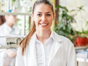 Young female scientist stands in the laboratory and smiles.